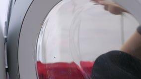 De vrouw in rode rubberhandschoenen wast een wasmachine met spons stock videobeelden