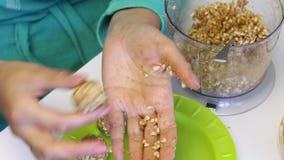 De vrouw rolt ballen voor het vullen popcake Van verpletterde die pinda's met andere ingrediënten worden gemengd Geëindigd lig op stock video