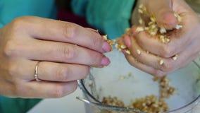De vrouw rolt ballen voor het vullen popcake Van verpletterde pinda's die met andere ingrediënten worden gemengd Close-up stock video