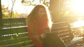 De vrouw in rood drinkt koffie en zitting op bank in park tijdens de herfstweer, gebruikend tablet Het rode hoofdmeisje controler stock video