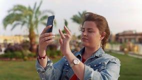 De vrouw in rood overhemd en jeansjasje maakt mobiele foto's van de gezichten, bezienswaardigheden bezoekend op vakantie, mobiele stock videobeelden