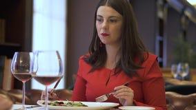 De vrouw in rood zit in restaurant en het eten van heerlijke salade stock footage
