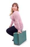 De vrouw in roze blouse zit op koffer Royalty-vrije Stock Fotografie