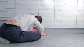De vrouw in roze rubberhandschoenen wast hard keukenmeubilair met doek, zittend op de vloer Achter mening stock videobeelden