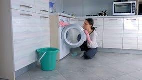 De vrouw in roze rubberhandschoenen wast wasmachine met doek, zittend op de vloer Zachte nadruk stock videobeelden
