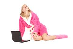 De vrouw in roze zit op de vloer met laptop royalty-vrije stock afbeeldingen