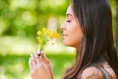 De vrouw ruikt gele bloemen Royalty-vrije Stock Foto's