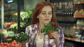 De vrouw ruikt verschillende huisinstallaties bij de supermarkt stock footage