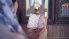 De vrouw in de Russische Orthodoxe Kerk met rood haar en een sjaal op haar hoofd steekt een kaars aan en bidt voor stock footage