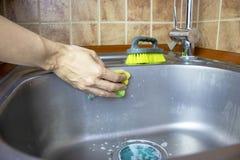 De vrouw ` s bebouwde handenwassen en maakt een gootsteen met een spons en een borstel schoon royalty-vrije stock foto