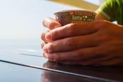 De vrouw ` s dient de kop van de sweaterholding van koffie op de zwarte houten lijst in Stock Afbeelding