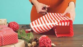 De vrouw ` s overhandigt bindende Kerstmisvakantie met de hand gemaakt heden in ambachtdocument met strenglint stock video