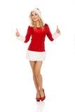 De vrouw in santa kleedt omhoog gesturing duimen Stock Foto