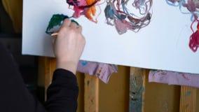De vrouw schildert beeld op canvas met olieverven in haar studio 4k stock videobeelden