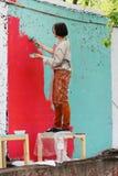 De vrouw schildert concrete omheining bij het Project ` van festival` Seizoenen in Moskou Stock Fotografie