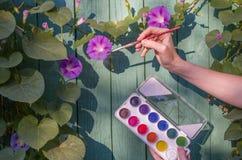 De vrouw schildert de bloemen in de tuin met waterverfverf Royalty-vrije Stock Foto's