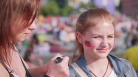 De vrouw schildert Duitse vlag op nicht` s wang stock video