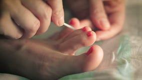 De vrouw schildert haar teennagels rode lak stock video