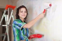 De vrouw schildert muur met rol stock afbeeldingen