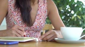 De vrouw schrijft in agenda royalty-vrije stock afbeelding