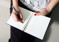 De vrouw schrijft op notitieboekje Stock Foto's