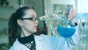 De vrouw schudt fles in een laboratorium stock footage