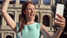 De vrouw selfie op mobiele telefoon dichtbij Colosseum in Rome, Italië Tiener die in langzame motie glimlachen