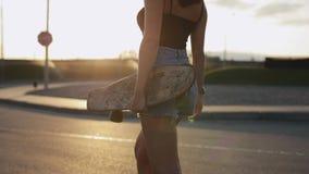 De vrouw skateboarder draagt haar skateboard in handen bij zonsondergang stock videobeelden