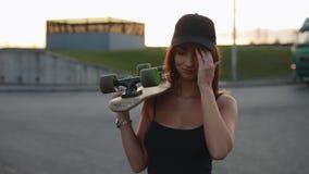 De vrouw skateboarder draagt haar skateboard op een schouder stock footage