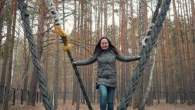 De vrouw slingert op een reusachtige houten schommeling in stadspark stock footage