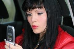 De vrouw is sms door mobiel stock afbeeldingen