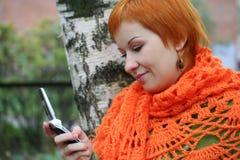 De vrouw is sms in mobilofoon stock afbeelding