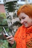 De vrouw is sms in mobilofoon stock afbeeldingen