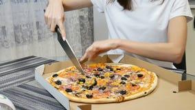 De vrouw snijdt een hete pizza met paddestoelen, kaas, maïs, olijven, rode uiringen en tomaten in kartondoos het gebruiken stock videobeelden