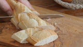 De vrouw snijdt Franse brood dichte omhooggaand op scherpe raad stock video