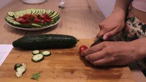 De vrouw snijdt groenten op een houten raad met messen dichte omhooggaand, tomaten en komkommers stock footage