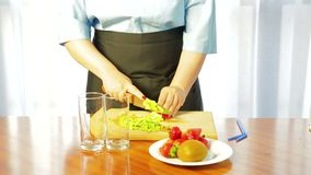 De vrouw snijdt rijpe kiwi met een mes op een houten raad op plakken stock video
