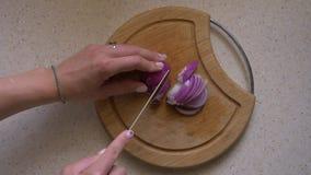 De vrouw snijdt rode uien op een houten raad in de keuken close-up, hoogste mening stock footage