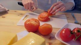 De vrouw snijdt tomaten op plastic raad, overhandigt close-up stock videobeelden
