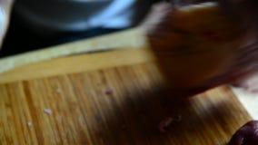 De vrouw snijdt varkensvleeskarkas in stukken stock videobeelden