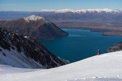 De vrouw snowboarder geniet van de majestueuze mening van Ohau-Sneeuwgebieden stock afbeeldingen