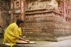 De vrouw sorteert graan bij de tempel van Pancharatna Govinda in Puthia, Bangladesh Stock Afbeeldingen