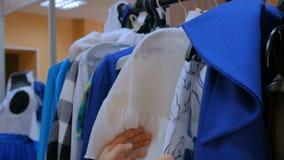 De vrouw sorteert uit hanger met kleren met de hand stock footage
