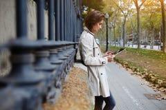 De vrouw speelt spelen op digitale tablet, terwijl vriend openlucht wacht royalty-vrije stock fotografie
