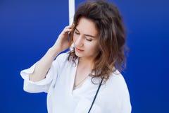 De vrouw spreekt door celtelefoon Stock Foto's