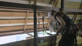 De vrouw steeplejack bereidt materiaal voor het werk aangaande het dak voor stock video