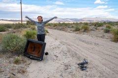 De vrouw stelt met een oude busted gebroken CRT televisie in het midden van de woestijn, dichtbij het Salton-Overzees van Califor stock afbeelding