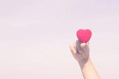 De vrouw steunt ter beschikking een rood hart stock fotografie