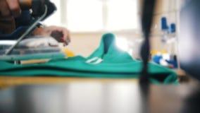 De vrouw strijkt doek in fabriek Het werken met textiel stock footage