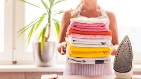 de vrouw strijkt kleren, gestreken kleren strijkend, wasserij, kleren, huishouden en objecten concept royalty-vrije stock foto